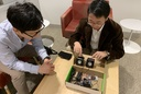 Sunghoon Ivan Lee, left, and Jie Xiong discuss how they will design a smaller device based on the larger prototype apparatus pictured.