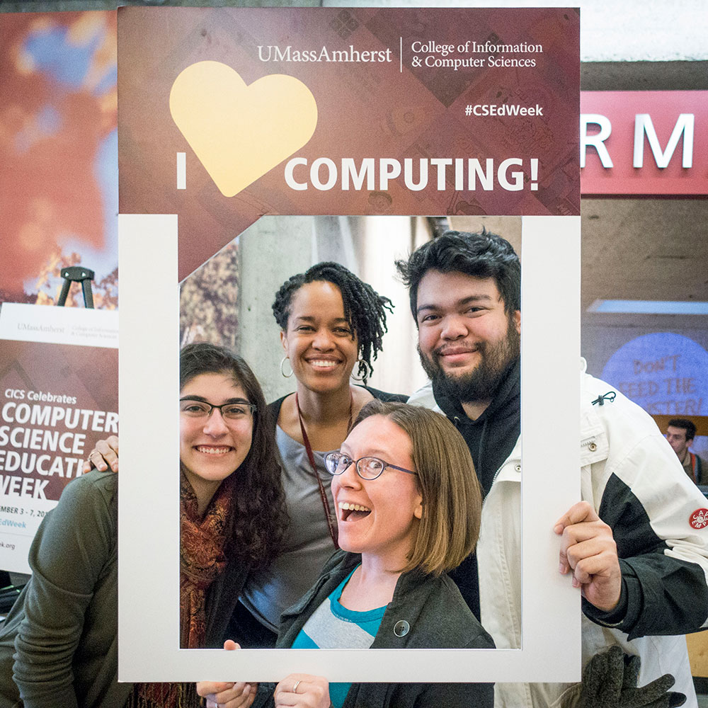 "A group holding ""I love computing"" poster frame"